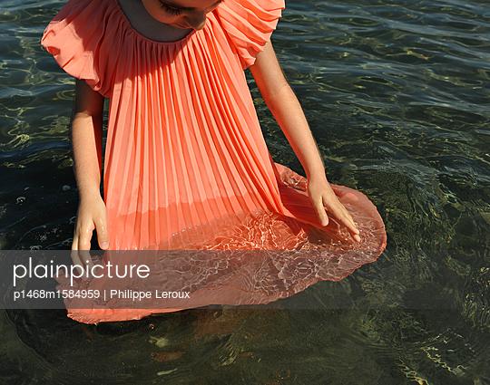 Kleines Mädchen im orangefarbenen Kleid spielt im Wasser - p1468m1584959 von Philippe Leroux