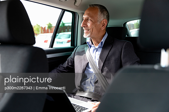 Businessman looking through window while sitting with laptop in car - p300m2287343 by Emma Innocenti