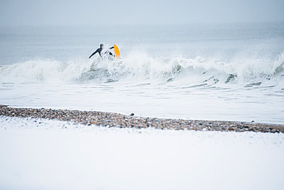 Man surfing during winter snow - p1166m2177110 by Cavan Images