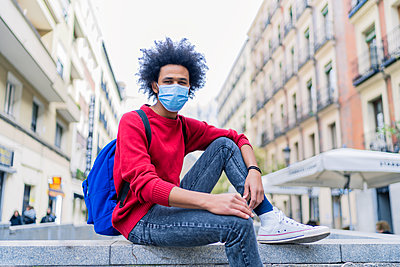 young man with afro hair sitting in the city - p1166m2255130 by Cavan Images