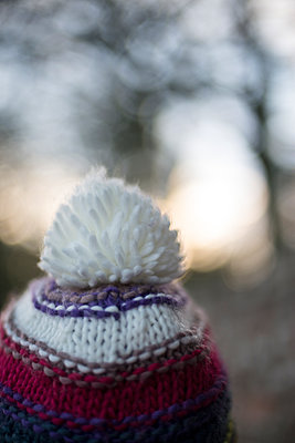 Person from behind, partial head only, wearing a colourful woolly hat with a white pom-pom before blurry landscape in wintry light. - p1433m1496384 by Wolf Kettler