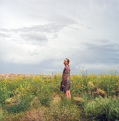 Woman standing on a flowered orchard - p1610m2181467 by myriam tirler
