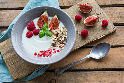 Bowl of natural yoghurt with fruit muesli, raspberries, figs and pomegranate seed - p300m2060415 by JLPfeifer