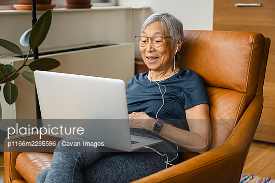 Portrait of senior woman smiling while using laptop at home - p1166m2285596 by Cavan Images