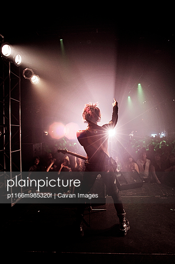 Rear view of man with arm raised performing at music concert - p1166m985320f by Cavan Images