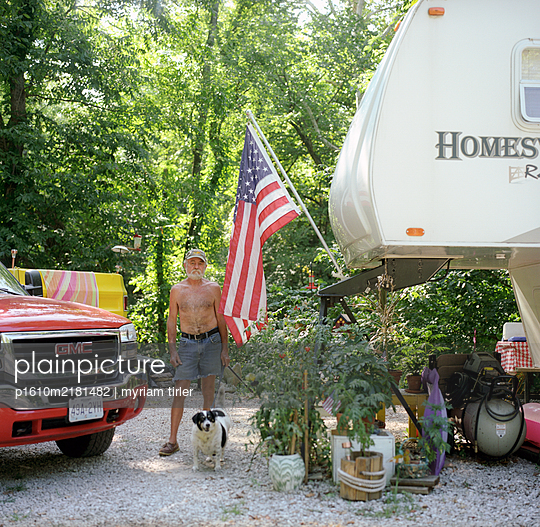 American man standing by his trailor with american flag - p1610m2181482 by myriam tirler