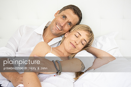 Happy couple cuddling on bed - p1640m2259618 by Holly & John