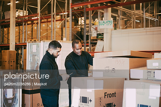 Male manual workers analyzing cardboard box at warehouse - p426m2238286 by Maskot