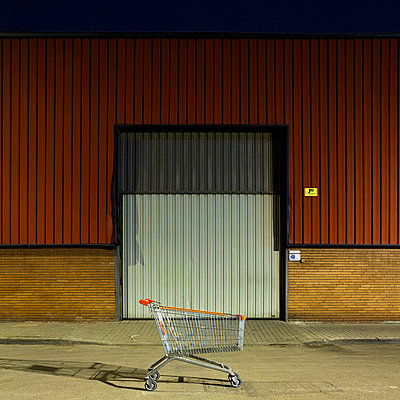 Shopping trolley left in front of a warehouse in Barcelona - p1072m829071 by Joan Seculi