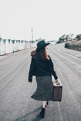 Woman with brown hair, long dress, cowboy hat, holding a suitcase - p1628m2195765 by Lorraine Fitch