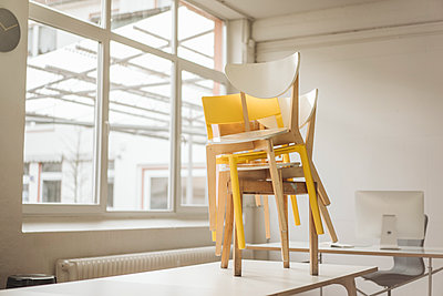 Stack of chairs standing on meeting table in a loft - p300m1356265 by Kniel Synnatzschke