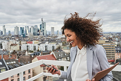 Happy mid adult businesswoman using mobile phone on rooftop - p300m2281422 by Annika List
