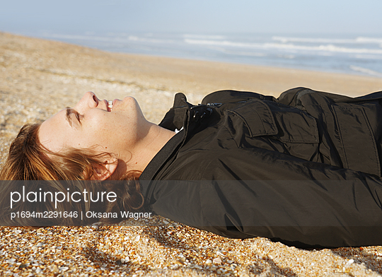 Smiling young man in love looking at the cloudless sky while lying on the beach in the morning - p1694m2291646 by Oksana Wagner
