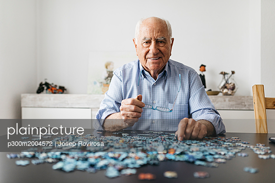 Senior man doing a jigsaw - p300m2004572 von Josep Rovirosa
