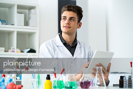 Thoughtful male scientist using digital tablet while looking away in laboratory - p300m2266143 by Giorgio Fochesato