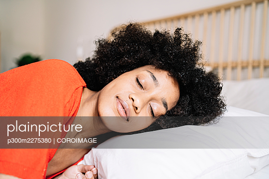 Young woman sleeping on bed at home - p300m2275380 by COROIMAGE