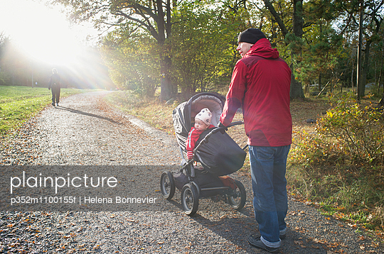 Sweden, Sodermanland, Nacka, man with son (12-17 months) walking in park - p352m1100155f by Helena Bonnevier
