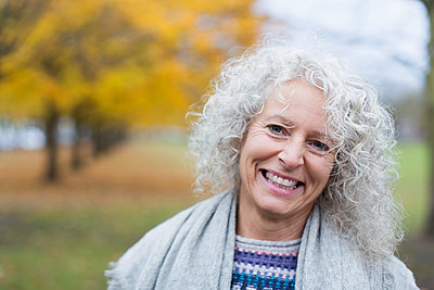 Portrait smiling senior woman in autumn park - p1023m1575879 by Tom Merton