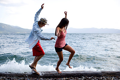 Two friends try to balance as they walk across a log on the shore of a lake in Idaho. - p1424m1501812 by Woods Wheatcroft