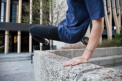 Spain, Madrid, man jumping over a wall in the city during a parkour session - p300m1175912 by Andrés Benitez
