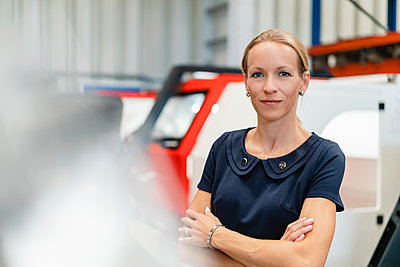 Confident businesswoman with arms crossed standing against machinery in industry - p300m2240125 by Daniel Ingold