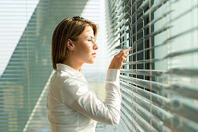 Businesswoman looking through blinds - p300m950953f by Westend61