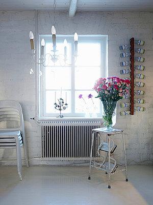 Flower vase kept on stool near window - p31225127 by Peter Carlsson