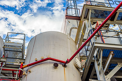 Low angle view of storage tanks and industrial piping at biofuel plant - p924m1480588 by Sue Barr