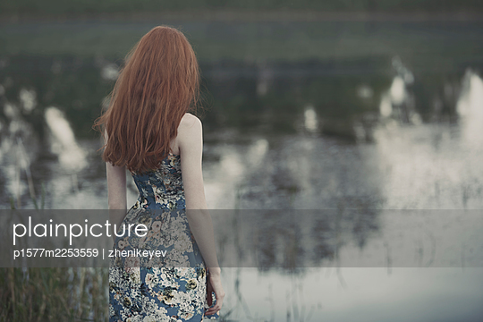 Redhead woman looking at the lake. Back view - p1577m2253559 by zhenikeyev