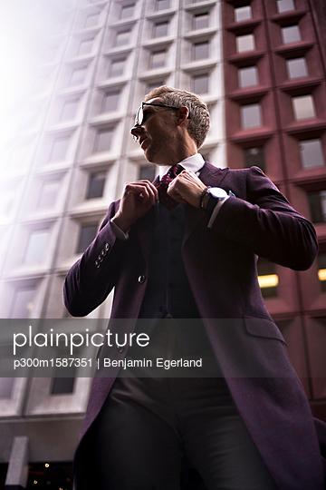 Fashion blogger Steve Tilbrook adjusting his tie - p300m1587351 von Benjamin Egerland
