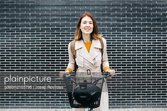 Portrait of smiling woman with e-bike at a brick wall - p300m2103795 by Josep Rovirosa