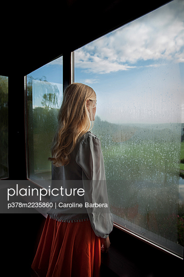 Woman looking out of window - p378m2235860 by Caroline Barbera