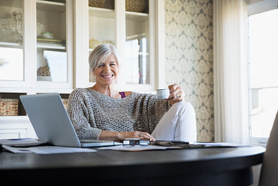Portrait smiling woman drinking tea at laptop - p1192m1078426f by Hero Images