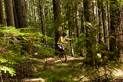 Young woman unicycling on trail - p1315m1484291 by Wavebreak