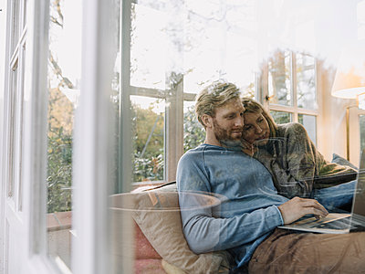 Man with wife using laptop in sunroom at home - p300m2166643 by Kniel Synnatzschke