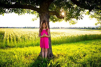 Portrait of little girl standing under apple tree with clover flowers in hands - p300m2199220 by Larissa Veronesi