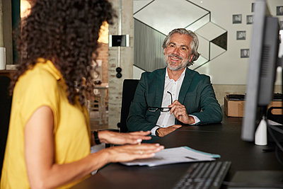 Smiling businessman looking at female colleague discussing in office - p300m2300427 by Rainer Berg