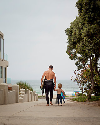 Caucasian father and son in wetsuits walking toward the ocean - p555m1479245 by Pacific Images