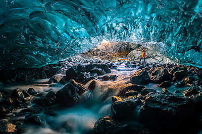 Vatnajokull glacier, Eastern Iceland, Iceland, Northern Europe. Man standing still at the entrance of a a crystal ice cave in winter. - p651m2007313 by Marco Bottigelli