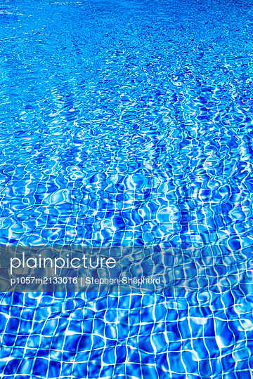 Sunlight reflects on the ripples of the surface of an outdoor swimming pool  - p1057m2133016 by Stephen Shepherd