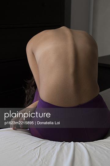 Junges Mädchen in lila Strumpfhose auf ihrem Bett - p1623m2215895 von Donatella Loi