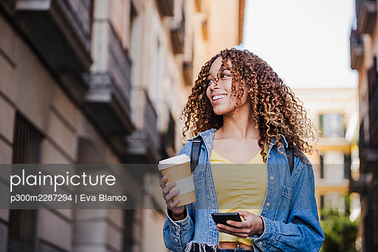 Beautiful woman looking away while holding reusable cup and smart phone in city - p300m2287294 by Eva Blanco