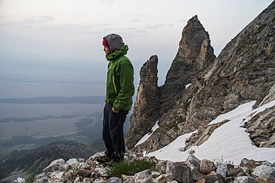 Side view of man with hands in pockets standing on mountain during winter - p1166m1545811 by Cavan Social
