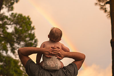 Rear view father carrying son on shoulders while looking at rainbow - p1166m1547333 by Cavan Social