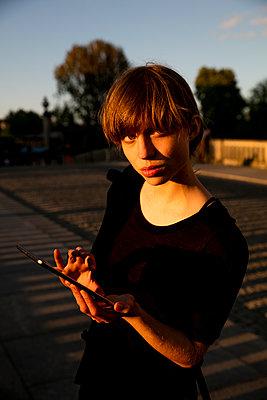 Junge Frau in der Abendsonne - mit Ipad auf der Monbijoubrücke  - p1212m1137011 von harry + lidy