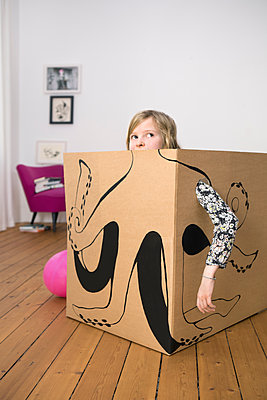 Girl inside a cardboard box painted with an octopus - p300m1450205 by Petra Stockhausen