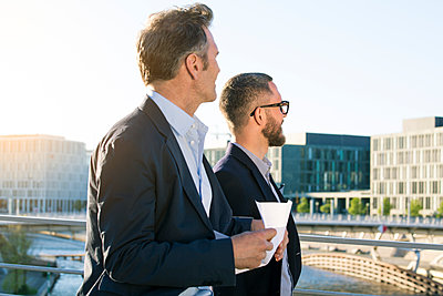 Two businessmen on a bridge in the city looking around - p300m2041882 by Florian Küttler