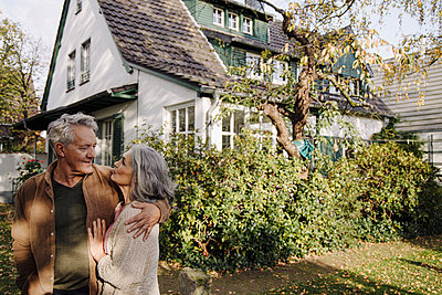 Senior couple in garden of their home in autumn - p300m2155226 by Gustafsson