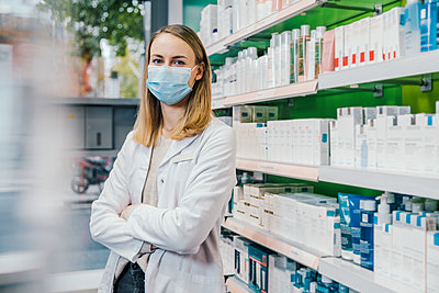 Pharmacist with arms crossed wearing protective face mask in chemist shop - p300m2243133 by Mareen Fischinger