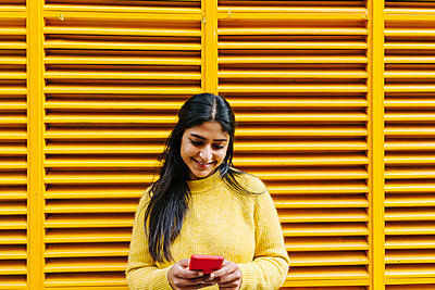 Woman with mobile phone standing at yellow wall - p300m2268313 by Xavier Lorenzo